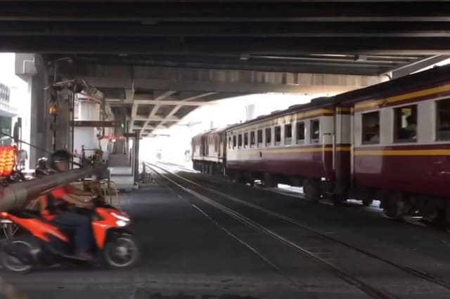 Impatient Thai motorcyclist clotheslined by level crossing barrier