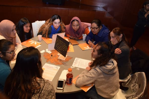 A group of students collaborates around a table.