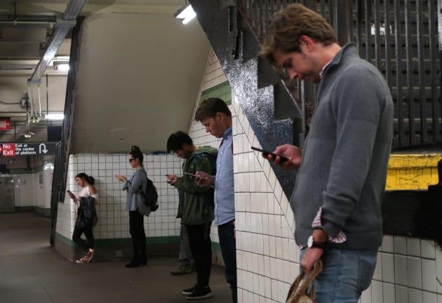 地下鉄でスマートフォンを利用するイメージ写真
