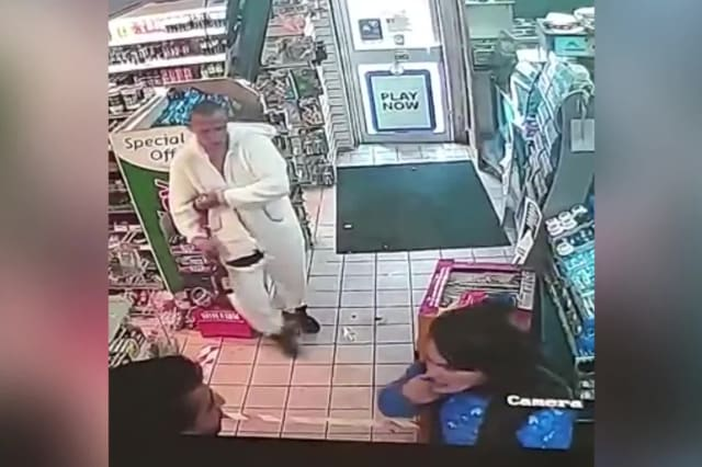 A thug dressed in a unicorn onesie confronted a shopkeeper while a woman spat in his face