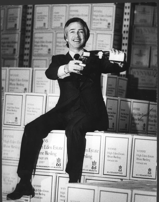 South Australian Premier Don Dunstan sitting on wine boxes from Wynn's High Eden Estate pouring a glass...