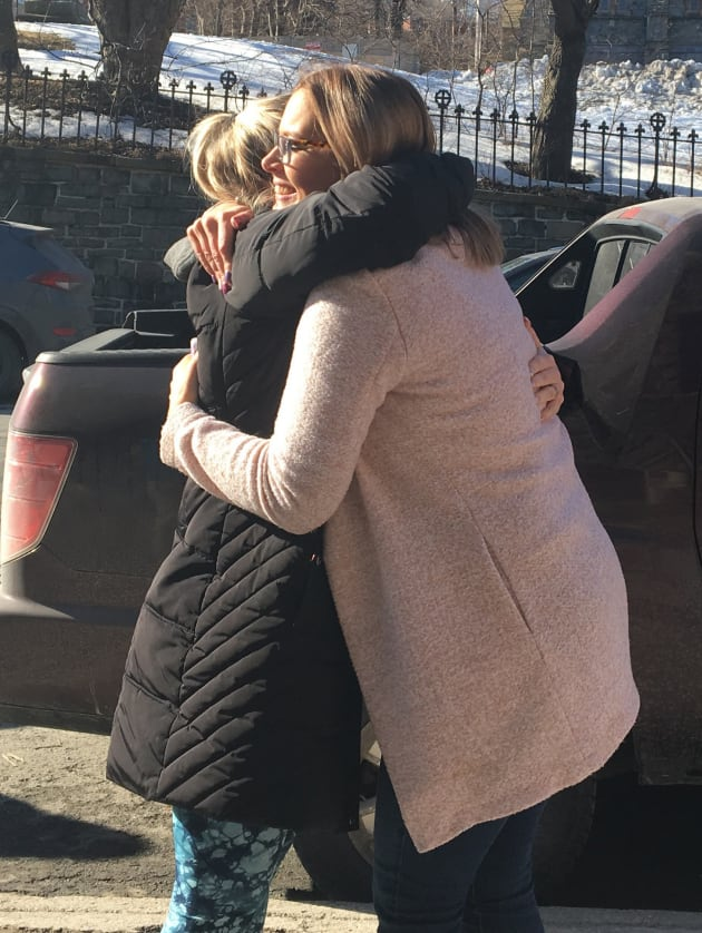 Andrea Gosse (right) is hugged by a supporter as she leaves the courthouse on Friday.