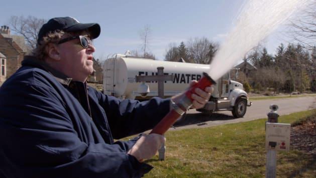 ミシガン州知事を突撃。人体に有害な鉛が検出されたフリントの水を知事の家に撒き散らすムーア監督。
