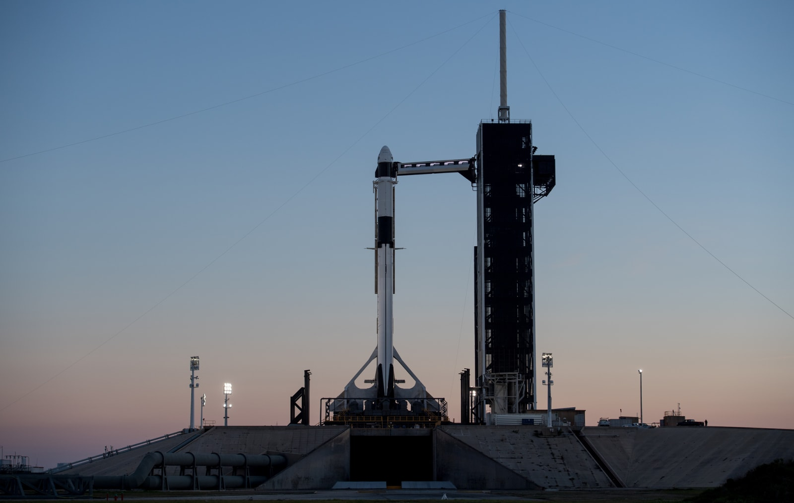 A SpaceX Falcon 9 rocket with the company's Crew Dragon spacecraft onboard is seen after being into a vertical position on the launch pad at Launch Complex 39A as preparations continue for the Demo-1 mission, Feb. 28, 2019 at the Kennedy Space Center in Florida.