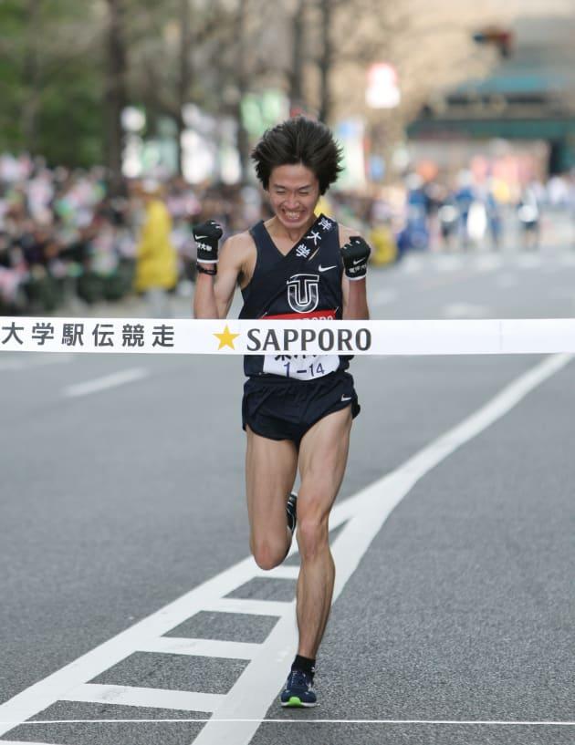ガッツポーズでゴールする、総合連覇を果たした東洋大学のアンカー高見諒=2010年1月3日、東京・大手町