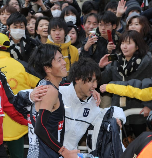 1位でゴールし笑顔を見せる東洋大アンカーの大津顕杜(手前左)。東洋大は2年ぶり4度目の総合優勝を果たした=2014年1月3日、東京・大手町