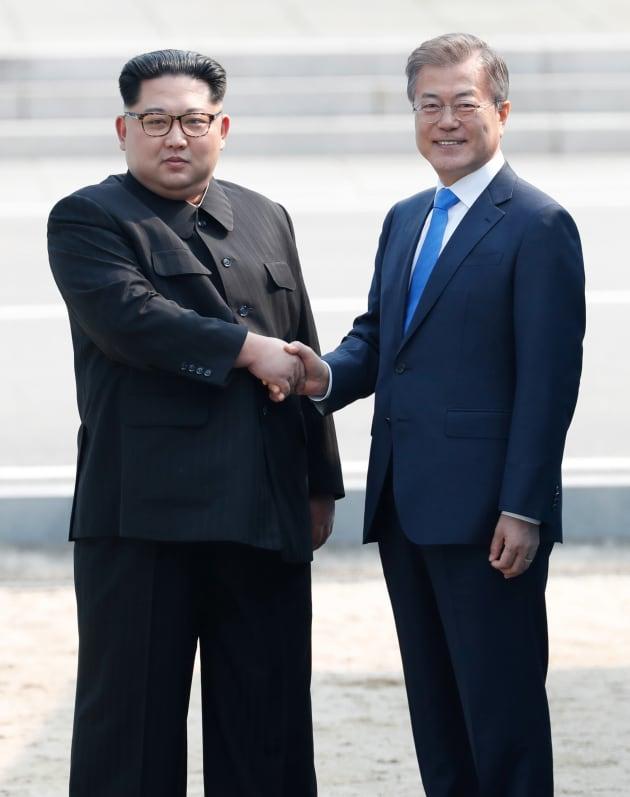 軍事境界線を歩いて越え、韓国側で文在寅大統領(右)と握手する北朝鮮の金正恩・朝鮮労働党委員長=4月27日、板門店