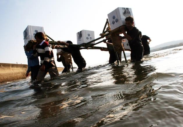「80リットルの水箱」を運ぶ人たち(2006年)