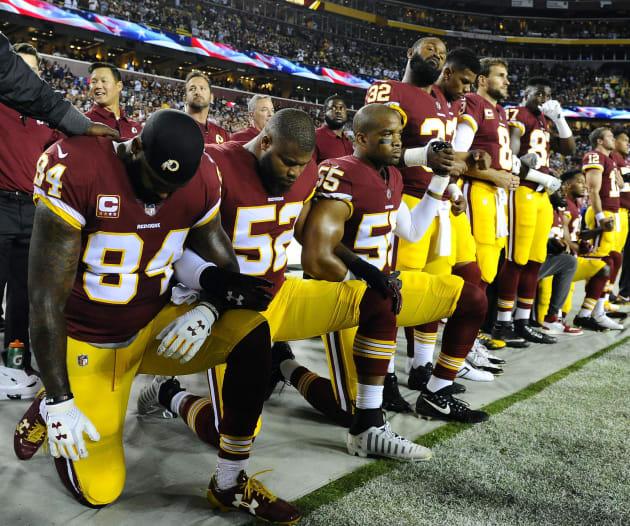 国歌斉唱時に膝をつくワシントン・レッドスキンズの選手たち=9月24日、メリーランド州