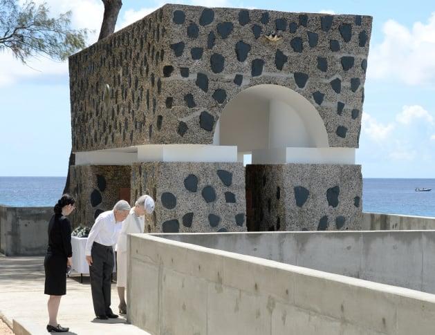 「西太平洋戦没者の碑」の前で、対岸のアンガウル島に向かって拝礼される天皇、皇后両陛下=2015年4月9日午前、パラオ・ペリリュー島[代表撮影]