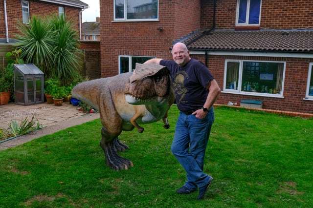 Wacky husband shocked his wife who told him to liven up their back garden with a gnome - by installing a 12ft tall replica of a T-Rex