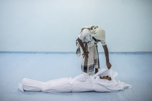 Al KHAWKHAH, YEMEN - SEPTEMBER 22: The body of a Yemeni fighter killed in Hodeidah is attended to by a friend at the morgue of a field hospital on September 22, 2018 in Al Khawkhah, Yemen. A coalition military campaign has moved west along Yemen's coast toward Hodeidah, where increasingly bloody battles have killed hundreds since June, putting the country's fragile food supply at risk. (Photo by Andrew Renneisen/Getty Images)