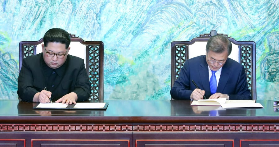 PANMUNJOM, April 27, 2018 -- South Korean President Moon Jae-in (R) and Kim Jong Un, top leader of the Democratic People's Republic of Korea (DPRK) sign for their joint declaration, titled the Panmunjom Declaration for Peace, Prosperity and Unification of the Korean Peninsula, at Peace House on the South Korean side of Panmunjom, on April 27, 2018. (Xinhua/Inter-Korean Summit Press Corps via Getty Images)