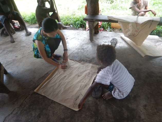 村人からの質問「どうやって妊娠するの?なんで双子が出来るの?」という質問に答えるため、即席教材を作成中。小さな女の子がお手伝いをしてくれました。