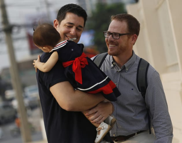 American Gordon Lake, right, and Spaniard Manuel Santos, left, walk with their baby Carmen at the Central Juvenile and Family Court in Bangkok, Thailand in 2016. They had a high-profile custody battle with a Thai surrogate mother who decided she wanted to keep the baby when she found out they were gay. Foreign surrogacy agreements are no longer legal in Thailand.