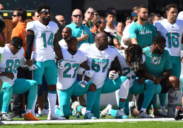 国歌斉唱の際、膝をついて抗議の意思を示したマイアミ・ドルフィンズの選手たち=9月24日、ニュージャージー州
