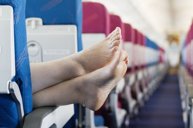 Woman resting feet on seat armrest of commercial airplane