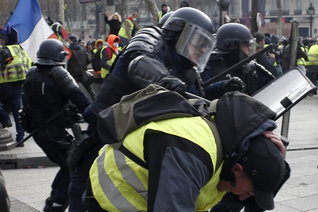 A riot police officer beats a demonstrator on the Champs-Elysees avenue Saturday, Dec. 8, 2018 in Paris. Crowds of yellow-vested protesters angry at President Emmanuel Macron and France's high taxes tried to converge on the presidential palace Saturday, some scuffling with police firing tear gas, amid exceptional security measures aimed at preventing a repeat of last week's rioting. (AP Photo/Rafael Yaghobzadeh)