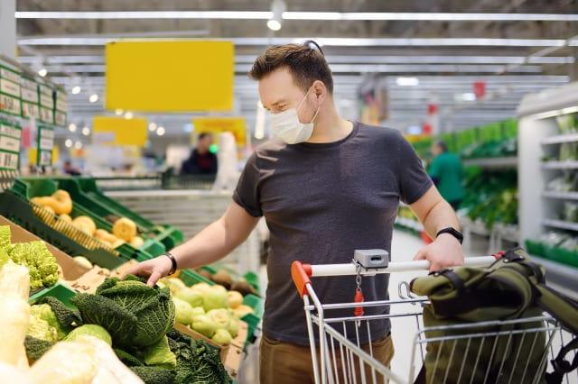 Man wearing disposable medical mask shopping in supermarket during coronavirus pneumonia outbreak