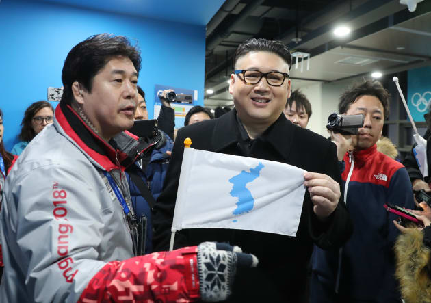Ice Hockey ? Pyeongchang 2018 Winter Olympics ? Women Preliminary Round Match - Korea v Japan - Kwandong Hockey Centre, Gangneung, South Korea ? February 14, 2018 - Kim Jong-un impersonator holds a Korean unification flag. REUTERS/Lucy Nicholson