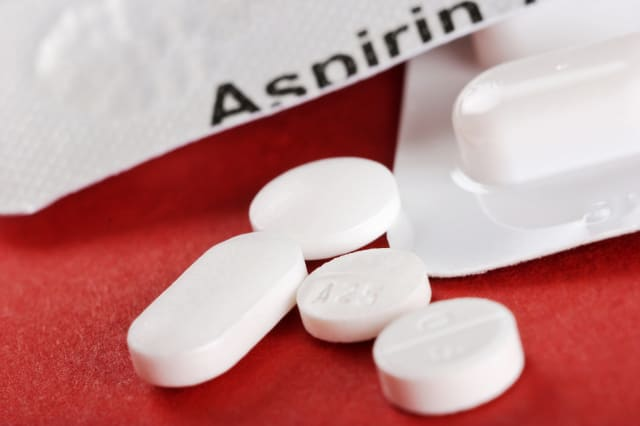 Close-up of four white tablets with aspirin container
