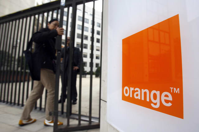 FILE - In this Oct.29, 2009 file photo, people enter the headquarters of France Telecom SA in Paris. French telecom giant Orange and seven former or current managers are going on trial Monday May 6, 2019, accused of moral harassment over a wave of employee suicides a decade ago. (AP Photo/Christophe Ena, File)