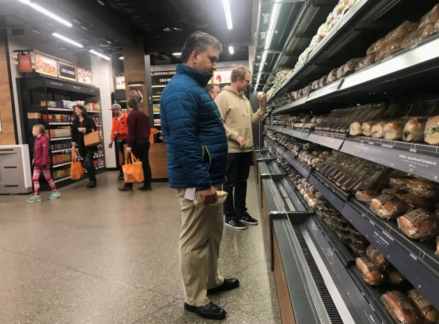 Los clientes buscan sándwiches y ensaladas empaquetados en la nueva tienda de Amazon en Seattle, Washington.