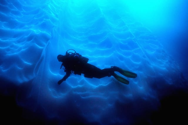 Diver against fluted ice at Antarctic Penninsula