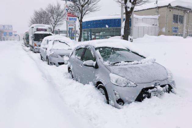 国道8号で立ち往生し、雪に埋もれた乗用車など=2018年2月7日、福井市