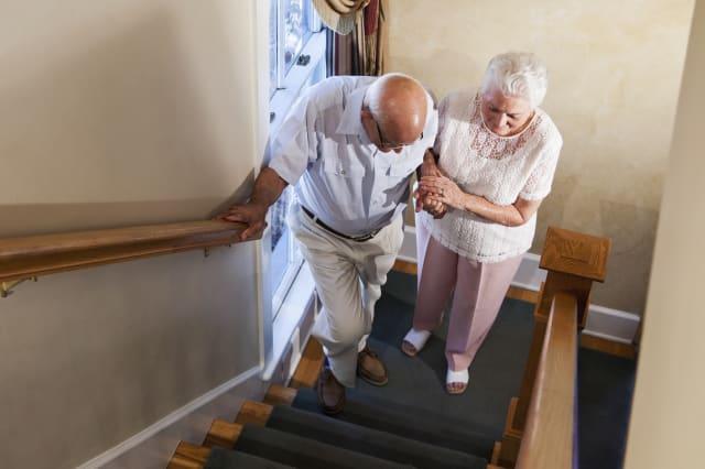 Senior woman helping husband climb staircase