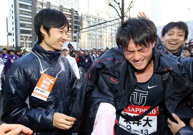 総合優勝を果たし、アンカーの斎藤貴志(右)を笑顔でねぎらう東洋大の柏原竜二主将=2012年1月3日、東京・大手町[代表撮影]