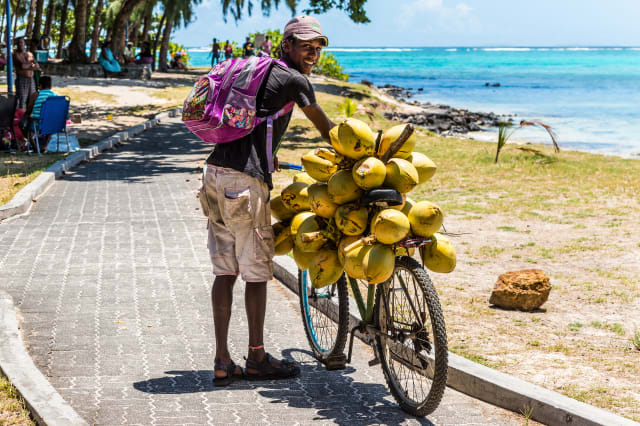 Man selling coconuts from his bike