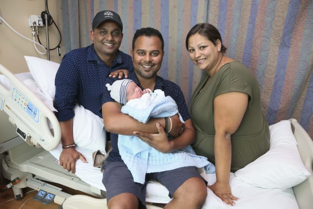 Asish Purushan holds baby Sidhnarth Jiwan Lall-Purushan with partner Krishneel Lall on the left and surrogate Mazyline McCarthy, at the Michael Garron Hospital, August 24, 2017.