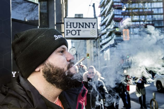 Cannaibis educator Jonathan Hirsh smokes a joint he purchased outside the Hunny Pot Cannabis Co. store...