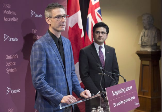 Former Ontario Attorney General Yasir Naqvi (right) listens as Mark Farrant speaks at the announcement of a juror support program in Hamilton, Ont. of the  on Jan. 31, 2017.