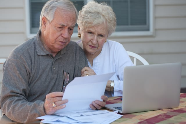 Senior couple working on home / personal finance using laptop with concerned expression