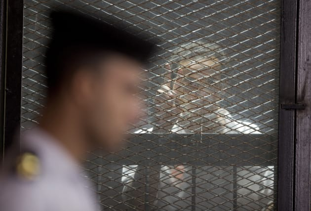 """Egyptian photojournalist Mahmoud Abu Zied, known by his nickname Shawkan, flashes a """"V"""" sign gesture as he listens to his trial in a soundproof glass cage inside a makeshift courtroom in Tora Prison in Cairo, Egypt, Saturday, July 28, 2018."""