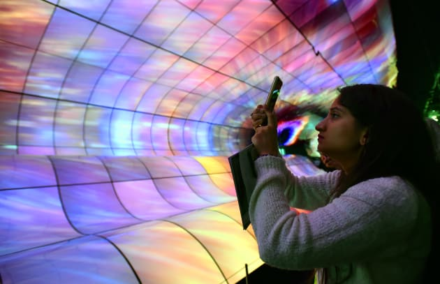 LAS VEGAS, NEVADA - JANUARY 08: An attendee photographs an exhibit of LG OLED TV screens at the LG booth at CES 2019 at the Las Vegas Convention Center on January 8, 2019 in Las Vegas, Nevada. CES, the world's largest annual consumer technology trade show, runs through January 11 and features about 4,500 exhibitors showing off their latest products and services to more than 180,000 attendees. (Photo by David Becker/Getty Images)