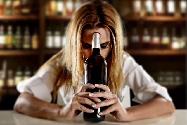 drunk alcoholic woman alone depressed with wine bottle in bar