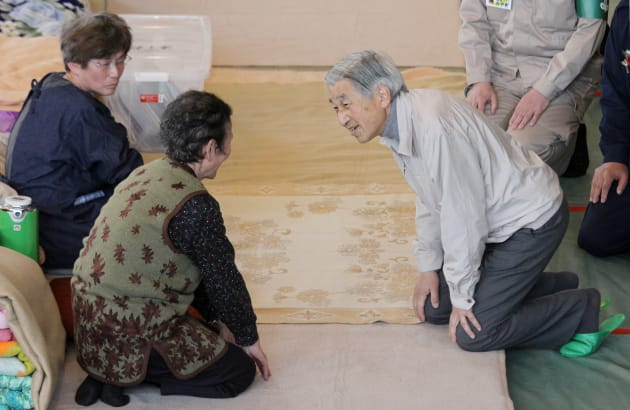 宮城県南三陸町の避難所で、被災者に声を掛けられる天皇陛下=2011年4月27日、同町の歌津中学校