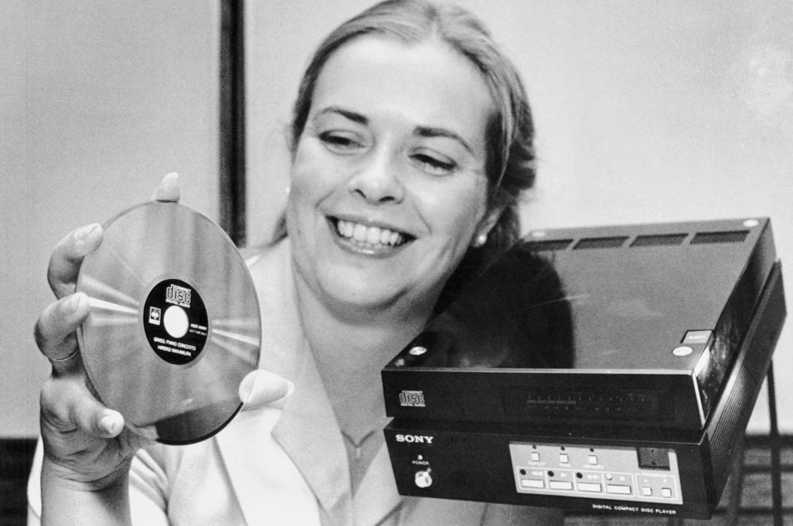 Woman Displaying Compact Disc and Player