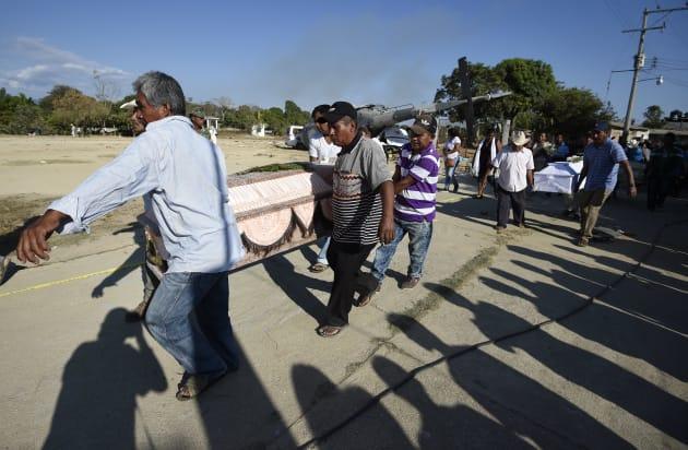 事故現場の遺体を棺に入れて運び出す犠牲者の遺族たち