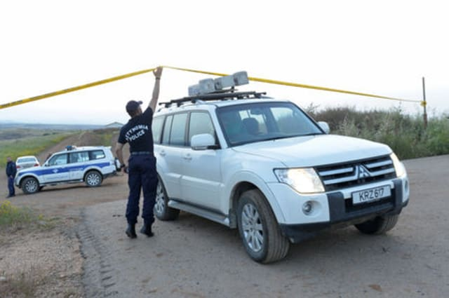 Police officers and rescuers are seen at the area where the body of a woman was discovered near the village of Orounta