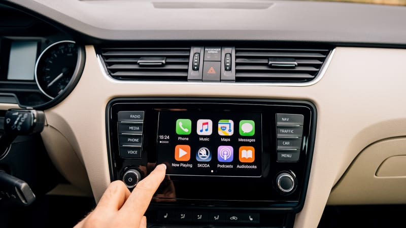 Man pressing home button on the Apple CarPlay