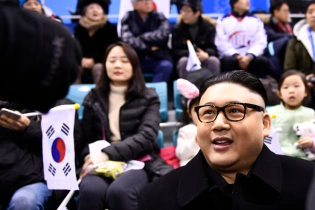 A Kim Jong Un impersonator sits with spectators during the final period of the women's preliminary round ice hockey match between Unified Korea and Japan during the Pyeongchang 2018 Winter Olympic Games at the Kwandong Hockey Centre in Gangneung, South Korea on February 14, 2018. / AFP PHOTO / Brendan Smialowski        (Photo credit should read BRENDAN SMIALOWSKI/AFP/Getty Images)