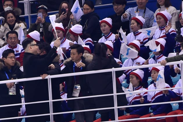 A Kim Jong Un impersonator cheers in front of North Korean cheerleaders during the final period of the women's preliminary round ice hockey match between Unified Korea and Japan during the Pyeongchang 2018 Winter Olympic Games at the Kwandong Hockey Centre in Gangneung, South Korea on February 14, 2018. / AFP PHOTO / Brendan Smialowski        (Photo credit should read BRENDAN SMIALOWSKI/AFP/Getty Images)