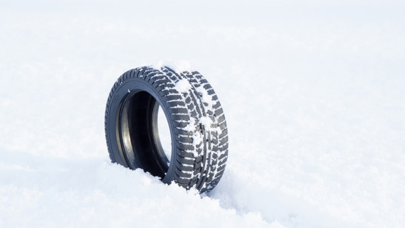 Black rubber tire rolling on the soft, fresh snow.
