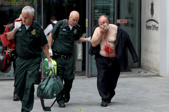 An injured man is helped by a medic outside the Home Office in London