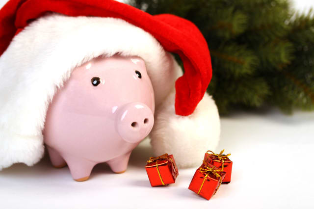 Part of piggy bank with Santa Claus hat and three little gifts and christmas tree standing on white background