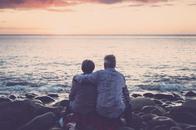 love and romance with adult  matures - elderly couple sitting and hugging each other looking at the sea at sunset relaxing. Concept of vacation, leisure time, relaxation -